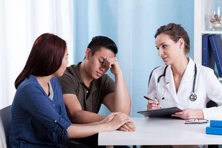 pacientes: Female doctor caucásico que habla con sus pacientes asiáticos