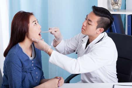 Aziatische mannelijke arts de behandeling van zijn vrouwelijke patiënt