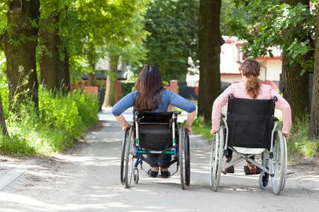 公園で車椅子で 2 人の女性の背面図 写真素材