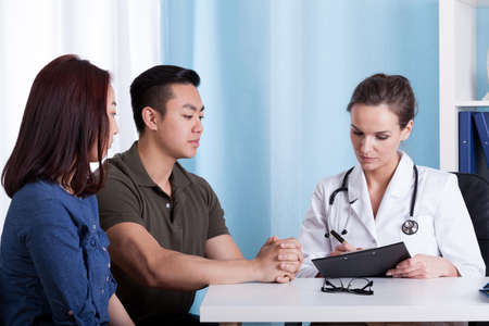Asian couple during visit at doctors office, horizontal photo