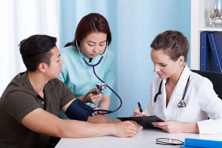 Asian female assistant taking blood pressure of male patient at doctors office photo