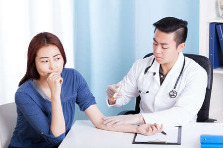 Asian young doctor and patient during doing injection, horizontal
