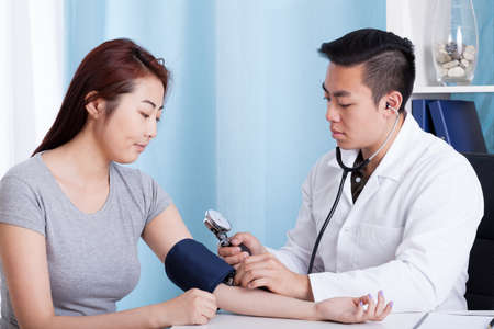 Asian male doctor taking blood pressure of a female patient