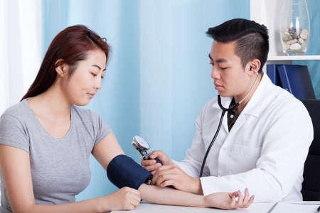Aziatische mannelijke arts die de bloeddruk van een vrouwelijke patiënt