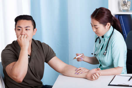 Young Asian nurse giving vaccination injection to male patient
