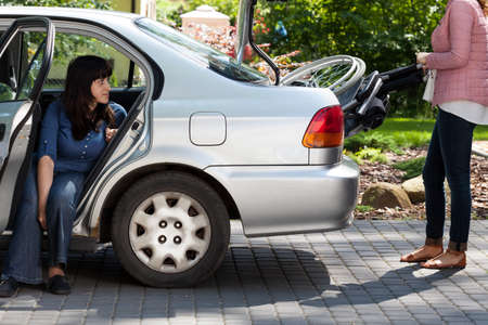 Girl taking wheelchair from car to provide mobility for disabled woman photo