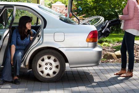tronco: Muchacha que toma la silla de ruedas de coche para proporcionar la movilidad de la mujer con discapacidad Foto de archivo