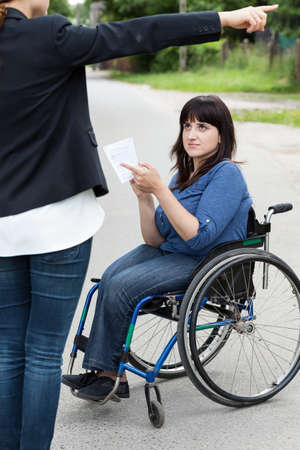 passerby: Young woman on wheelchair asking a female passerby about directions