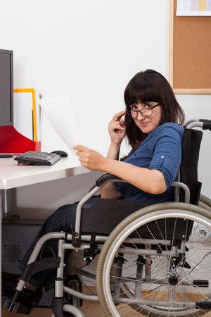 persona en silla de ruedas: Joven lisiado en silla de ruedas de trabajo en su oficina, vertical Foto de archivo