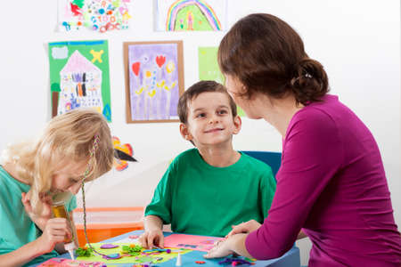 helps: The teacher helps children to art lessons Stock Photo