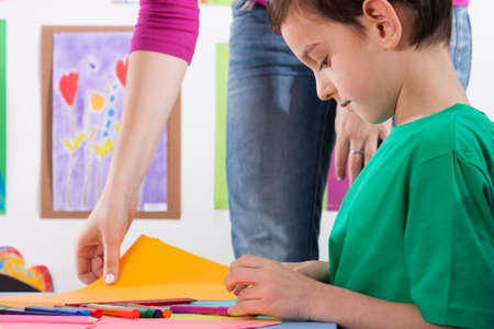 home school: A young boy prepares the card for art lessons Stock Photo