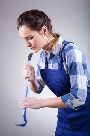 handywoman: A young handywoman wearing overalls focused on fixing