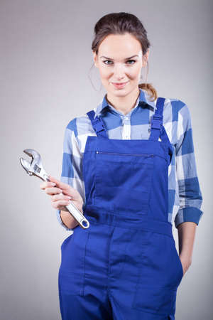 handywoman: A beautiful handywoman in overalls holding pillers