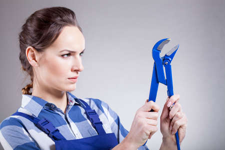 striving: A woman striving to use a monkey wrench
