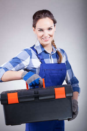 handywoman: A smiling handywoman holding a big toolbox at work