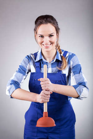 A handywoman in a working outfit holding a plunger photo