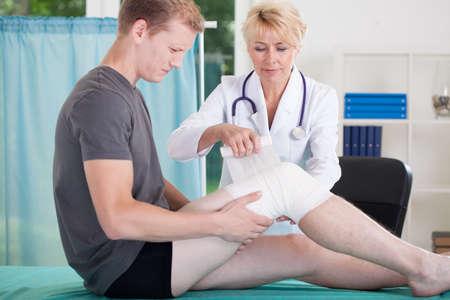 pierna rota: Hombre con lesión en la rodilla en la sala del médico Foto de archivo