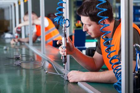 assembly: Hombres durante el trabajo de precisión en la línea de producción, horizontal
