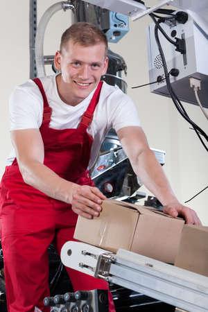 cinta transportadora: Hombre sonriente joven que poner cajas en la cinta transportadora automática Foto de archivo