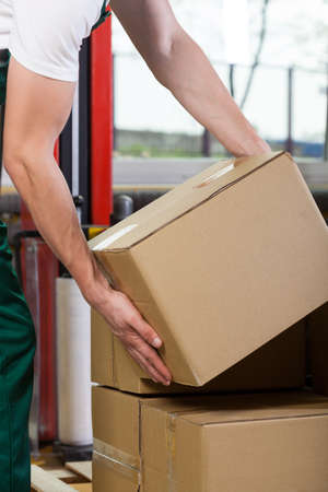cardboards: Close-up of a foremans hands lifting box at storehouse Stock Photo