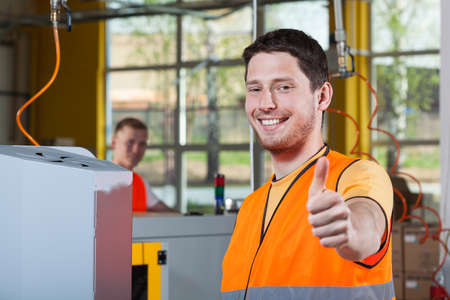 thumbs up sign: Machine operator in protective vest showing thumbs up sign Stock Photo