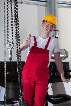 Blue-collar worker standing near to lifting equipment and showing thumbs up sign photo