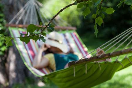 descansando: Mujer que duerme en una hamaca en el jardín Foto de archivo