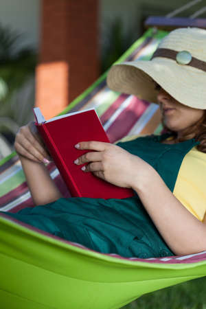 Woman reading book on a hammock, vertical photo