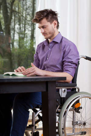capable: Capable disabled man reading a book at home