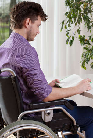 capable: Capable disabled man on whellchair reading a book