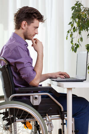 man using computer: Disabled man using a laptop at home