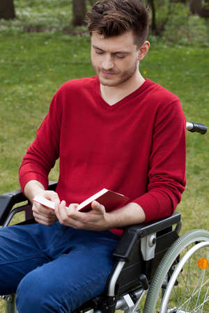 capable: Capable disabled reading a book outdoors Stock Photo