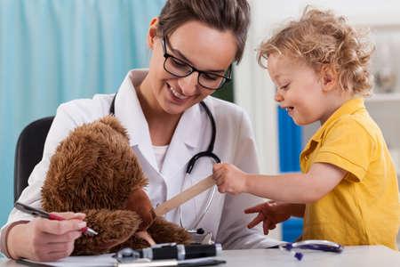 Female doctor and happy little boy examining a teddy bear 版權商用圖片 - 29943055
