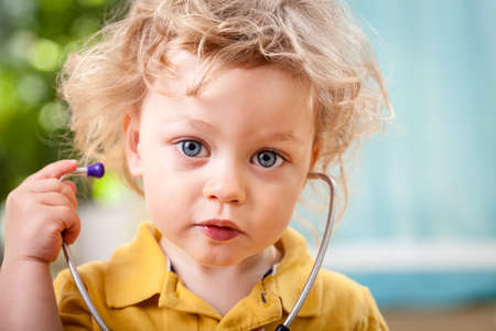 kid at doctor: Portrait of a cute little boy with stethoscope, horizontal