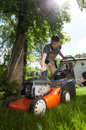 Man cutting grass in his yard using lawn mower photo