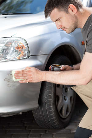 waxing: Man applying polish to removing scratches, vertical