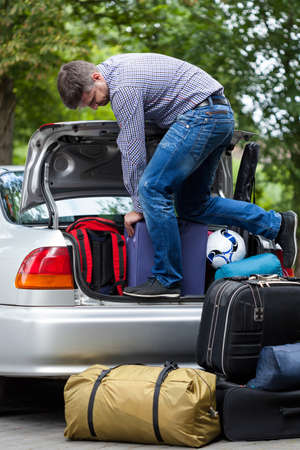 Man using his strength to packing luggage into car trunk Imagens