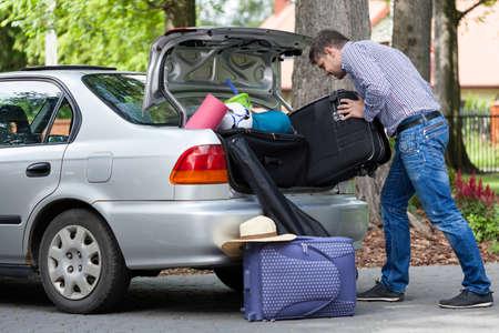 여행 가방을 차에 넣으려고하는 남자의 가로보기 스톡 콘텐츠