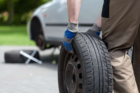 Close-up of a man rolling a spare wheel