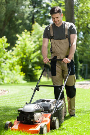 mow: Man in work overalls mowing lawn, vertical