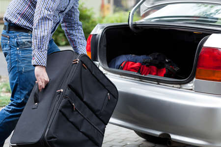 Close-up of a man putting suitcases in car trunk for a journey