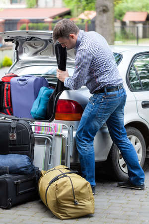 Vertical view of a man packing car for vacation photo