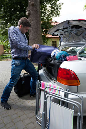 car trunk: Man pushing luggage into trunk of his car, vertical