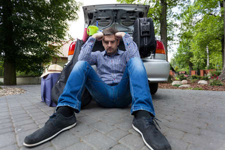 Upset man and car full of luggage bags before the family vacation photo