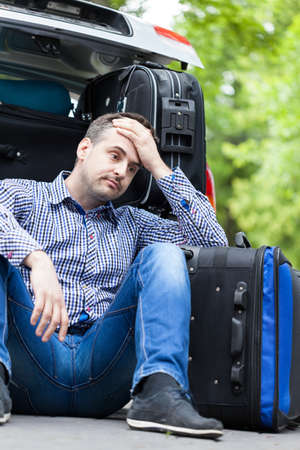 Man having problem with packing family luggage into a car photo