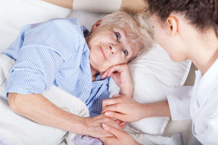 Elderly woman in bed and her nurse photo