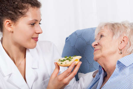 Horizontal view of nurse feeding elderly woman photo