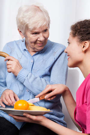 Nurse and elderly woman eating fruits, vertical photo