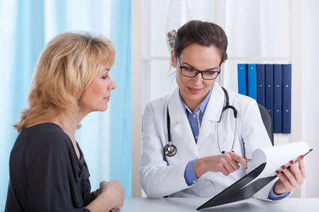 explaining: Doctor showing patient test results in office