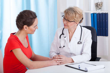 Mature Lady doctor advises the patient in the office